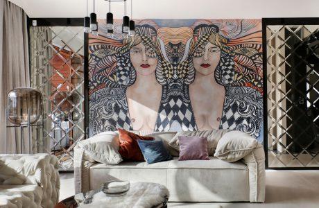 elegancka jasna sofa na tle dużego obrazu z dwoma kobietami