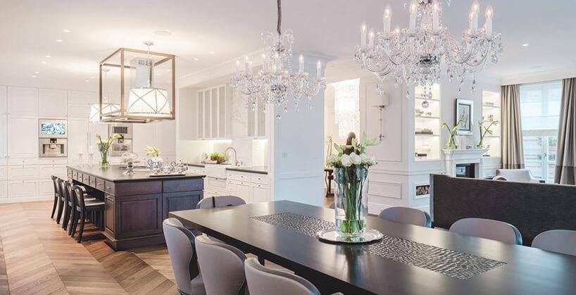eleganckie wnętrze rezydencji od Taff Architekci jasna jadalnia zdużym ciemnym stołem iszarymi krzesłami na tle białej kuchni