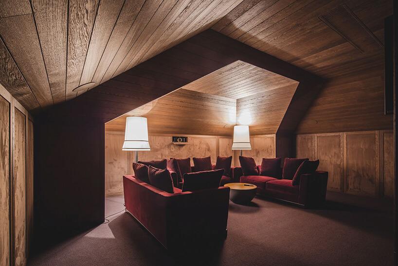 eleganckie wnętrze rezydencji od Taff Architekci wyjątkowy pokój wykończony drewnem ztrzema bordowymi sofami