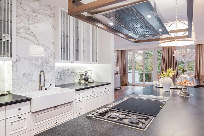 eleganckie wnętrze rezydencji od Taff Architekci biała kuchnia wykończona kamieniem zdużą wyspą zszarym blatem
