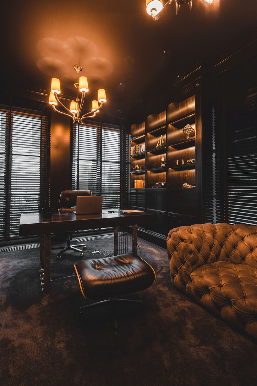 eleganckie wnętrze rezydencji od Taff Architekci ciemny gabinet zwyjątkową sofą obok masywnego biurka