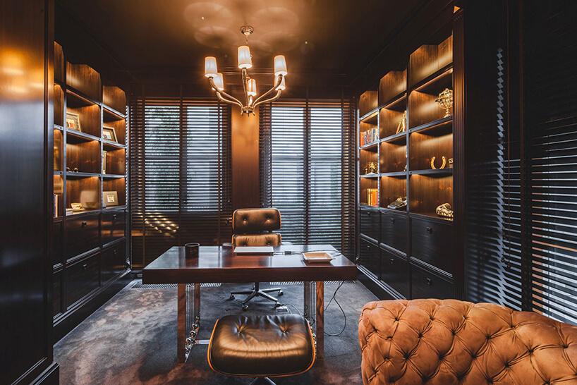 eleganckie wnętrze rezydencji od Taff Architekci masywne biurkow zeleganckim skórzanym fotelem pomiędzy dwoma masywnymi meblami