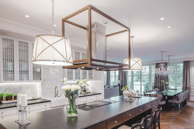 eleganckie wnętrze rezydencji od Taff Architekci biała kuchnia połączona zjadalnią zdrewniana podłogą