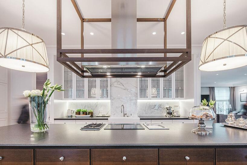 eleganckie wnętrze rezydencji od Taff Architekci duża wyspą zduży wyciągiem na tle białej kamiennej kuchni