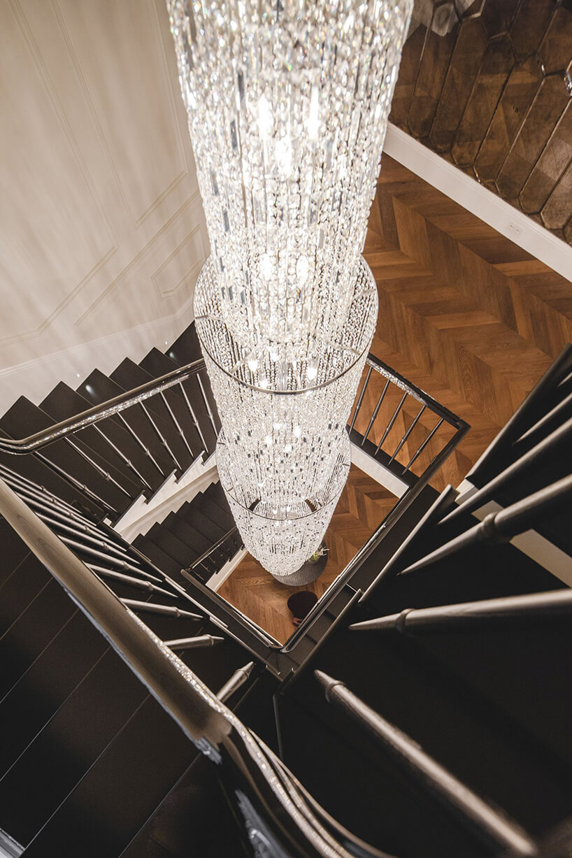 eleganckie wnętrze rezydencji od Taff Architekci ciemne schody zdługi żyrandolem