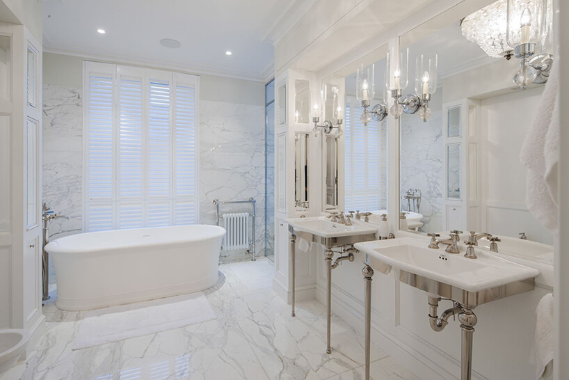 eleganckie wnętrze rezydencji od Taff Architekci biała kamienna łazienka zdużą wanną idwoma umywalkami zeleganckimi metalowymi nogami