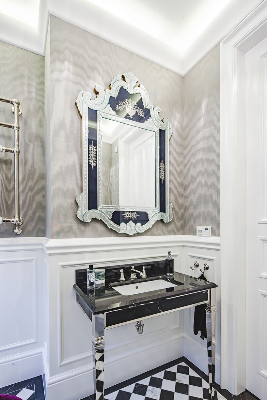 eleganckie wnętrze rezydencji od Taff Architekci białą toaleta zczęściowo szarą ścianą zeleganckim lustrem na umywalką zabudowaną czarnym kamieniem