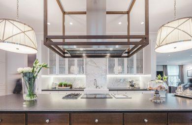 eleganckie wnętrze rezydencji od Taff Architekci duża wyspą z duży wyciągiem na tle białej kamiennej kuchni