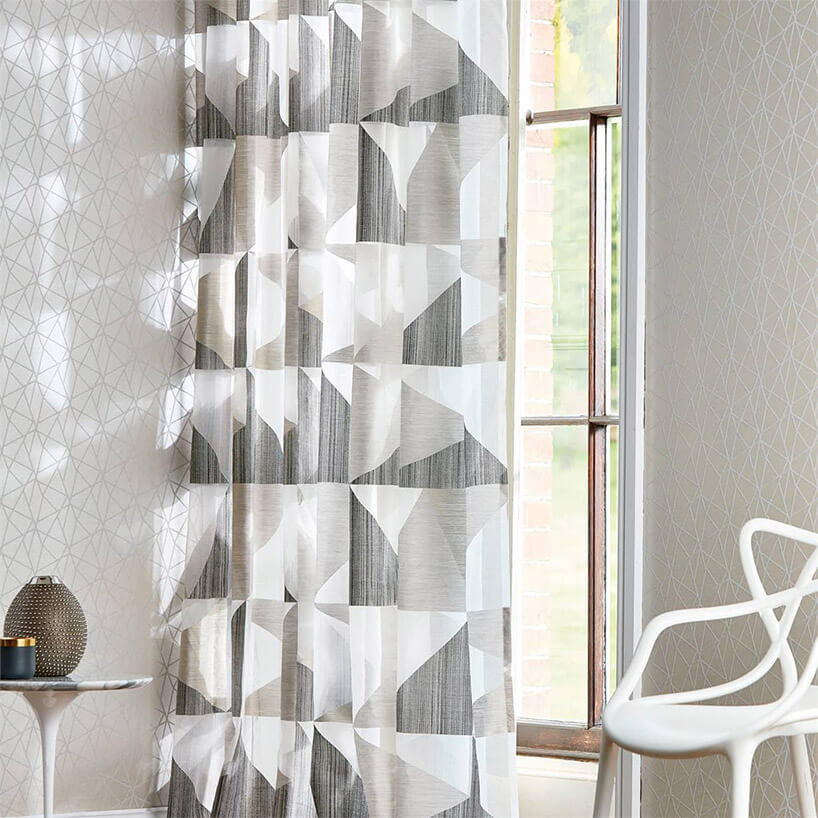 białe krzesło marmurowy stoliczek na tle szarej tapety izasłony