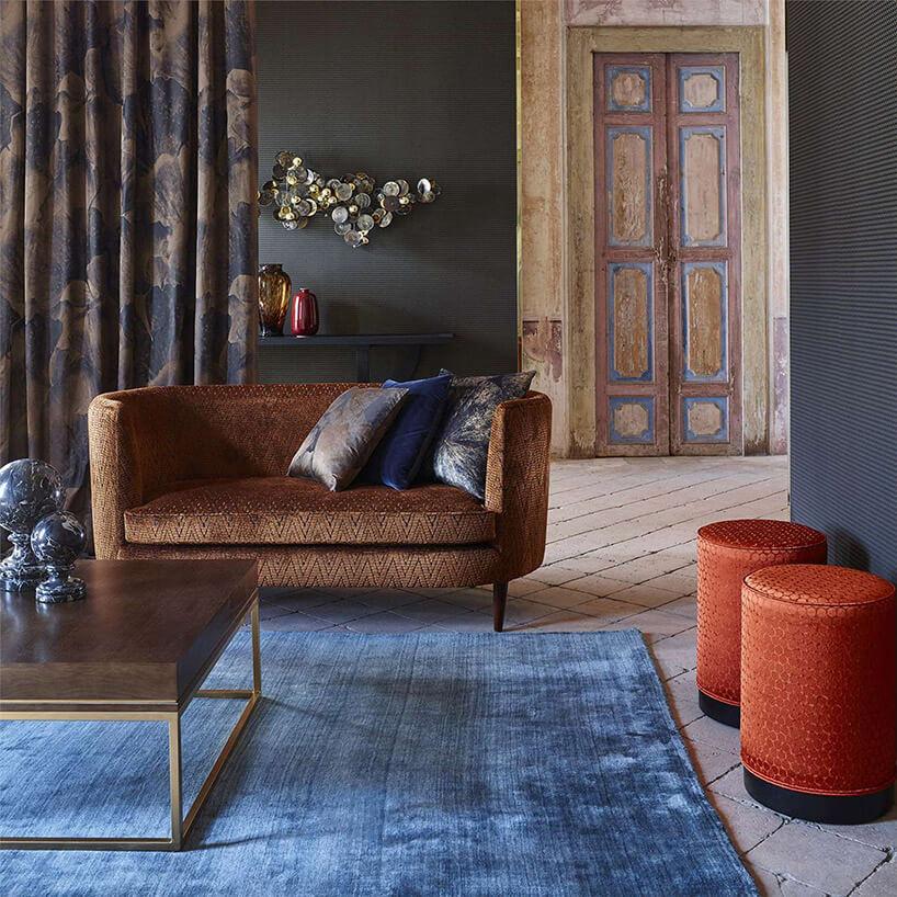 brązowa kanapa stolik iczerwone pufy na niebieski dywanie