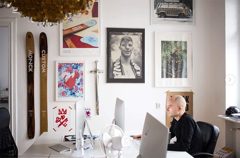 ściana pełna plakatów imężczyzna siedzący przy jednym ze stanowisk komputerowych