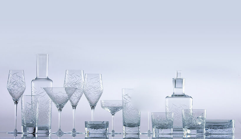 Kieliszki, szklanki ikarafka stojące na szaro=niebieskim tle