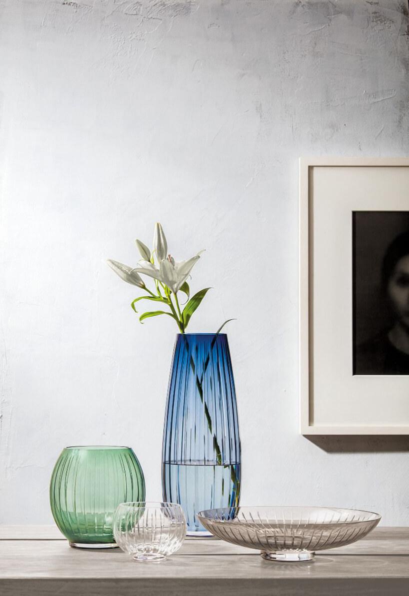 Niebieski ozielony wazon stojący na stole na tle szarej ściany zobrazem
