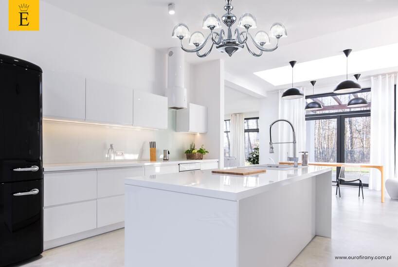 biała kuchnia zwyspą czarną zabudową AGD ifirankami Eurofirany