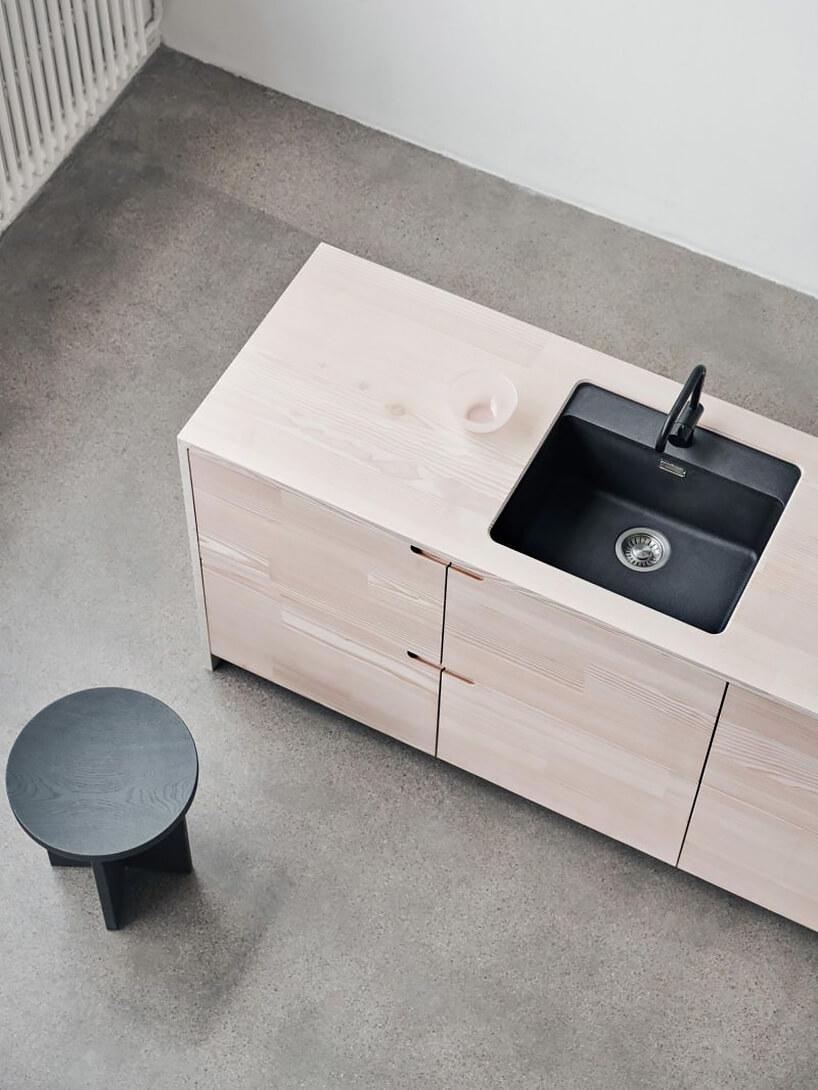 nowoczesna drewniana szafka kuchenna zosadzonym czarnym małym zlewem ibaterią nagrodzona wEuropean Product Design Award 2019