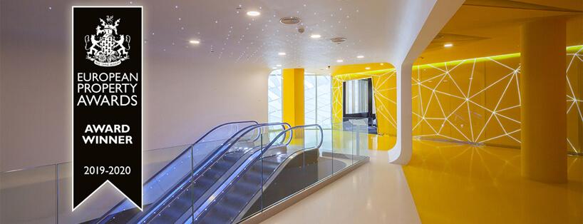 schody ruchome wMori Cinema na tle żółtej ściany isufitu zmałymi światełkami
