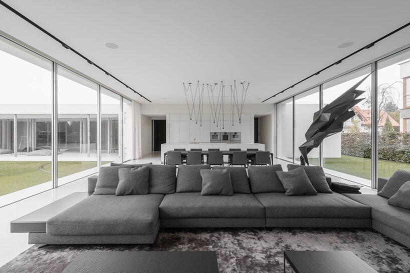 białe wnętrze Dom kwadrantowego zdużą szara sofą na tle szarego stołu zkrzesłami ibiałej kuchni