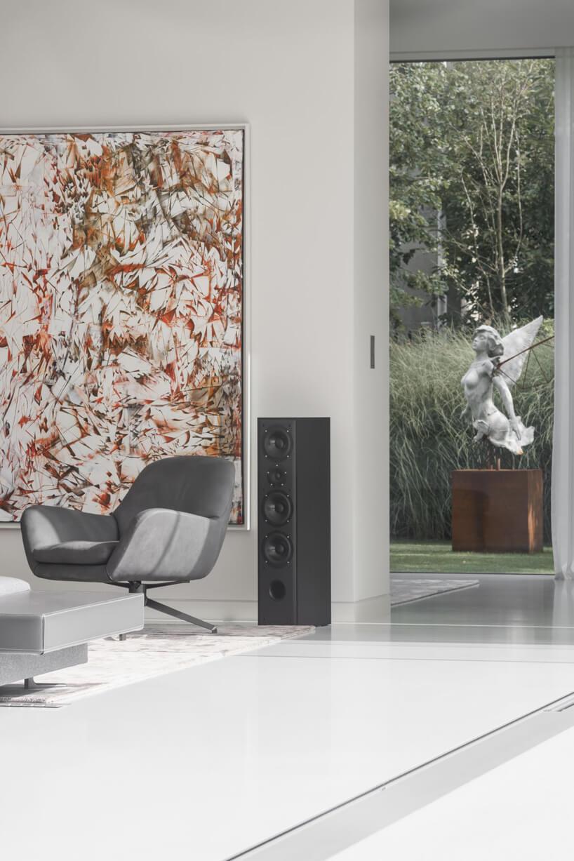 białe wnętrze Domu kwadrantowego zszarym fotelem obok czarnego głośnika na tle wzorzystego dużego obrazu