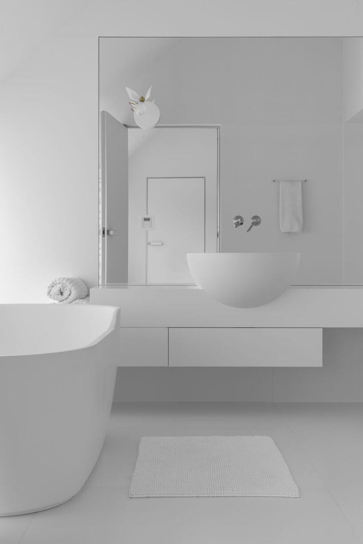czysto biała łazienka zdużym lustrem obok białej wanny