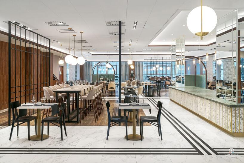 wnętrze części restauracyjnej Metropolo róznymi stolikami pod dużymi biało złotymi lampami