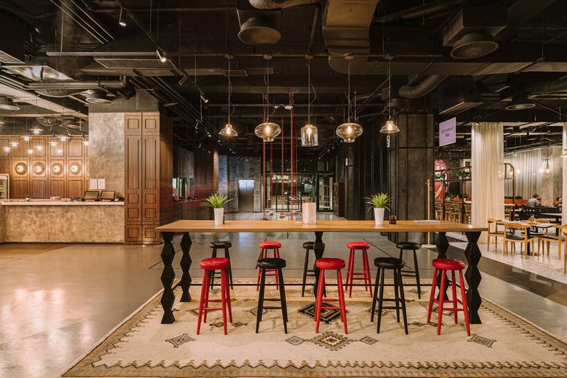 recepcja ipoczekalnia wibis Styles Sarajevo zdużym drewnianym stołem zczarnymi iczerwonymi stołkami