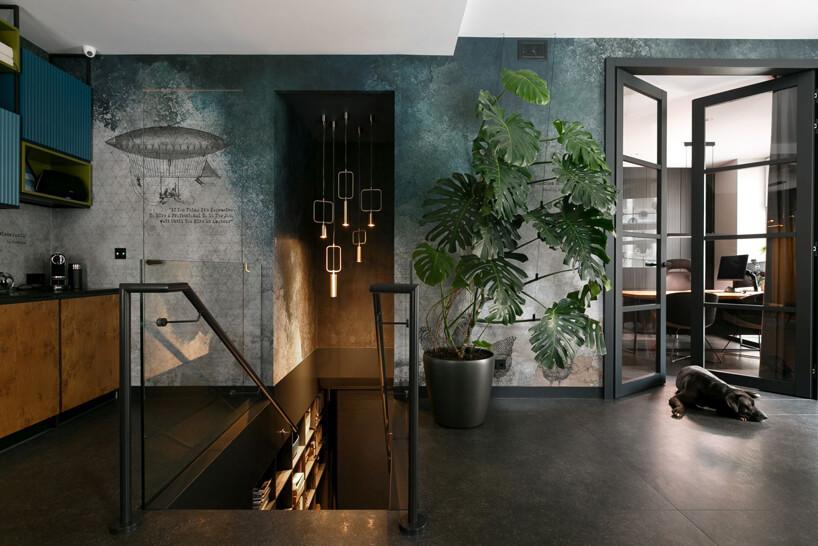 eleganckie ciemne wnętrze Siedziba MIKOŁAJSKAstudio zwąskimi ciemnymi schodami ze szklaną balustradą