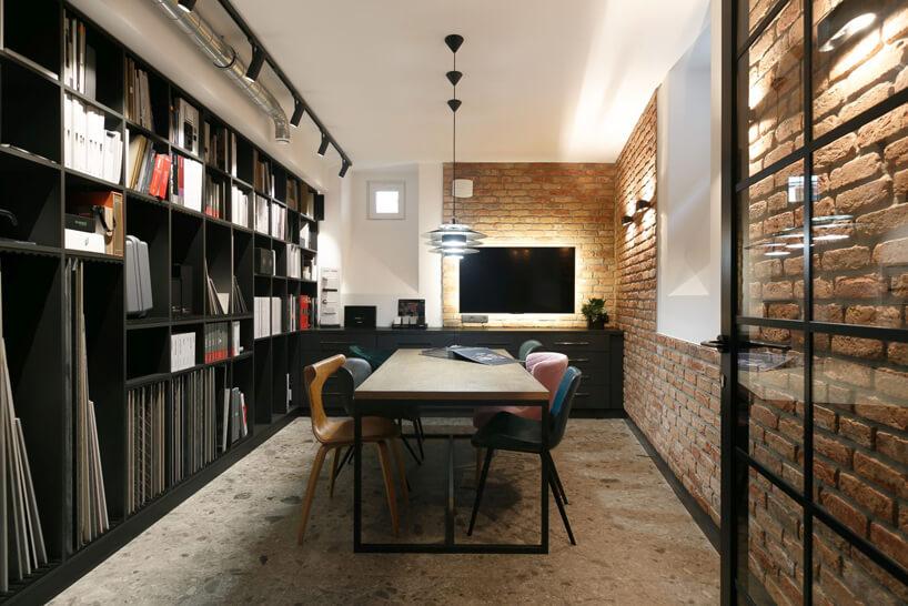 eleganckie jasne wnętrze Siedziba MIKOŁAJSKAstudio sala konferencyjna ze ścianami zcegłą ze stołem zsześcioma rożnymi fotelami