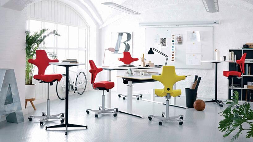 czerwone iżółte nowoczesne ergonomiczne krzesła biurowe Peter Opsvik wbiałym biurze