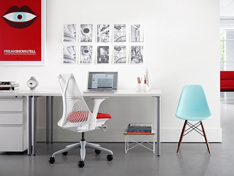 białe nowoczesne krzesło biurowe Sayl od Herman Miller wjasnym biurze zczerwonym plakatem