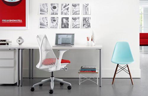 białe nowoczesne krzesło biurowe Sayl od Herman Miller w jasnym biurze z czerwonym plakatem