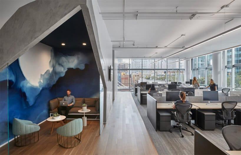 przestrzeń biurowa zniebieskim elementem oraz dużą ilością szary krzeseł oraz biurek