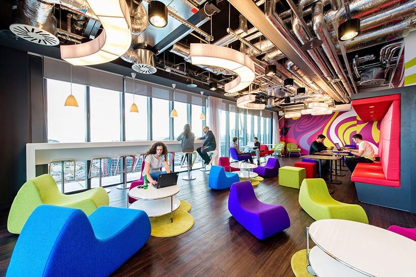 przestrzeń do pracy zzielonymi, niebieskimi iczerwonymi krzesłami przy dużych oknach