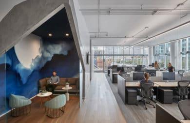 przestrzeń biurowa z niebieskim elementem oraz dużą ilością szary krzeseł oraz biurek
