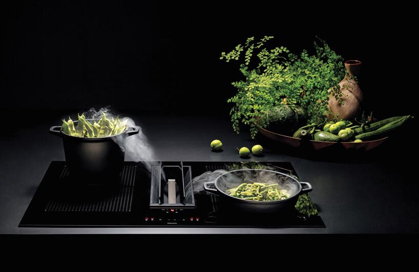 czarna płyta indukcyjna ze zintegrowanym okapem podczas gotowania zielonych warzyw