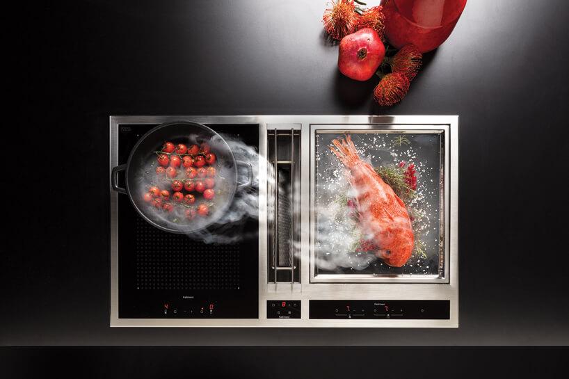 czarna ze srebrną ramką płyta indukcyjna ze zintegrowanym okapem podczas gotowania czerwonej ryby ipomidorów