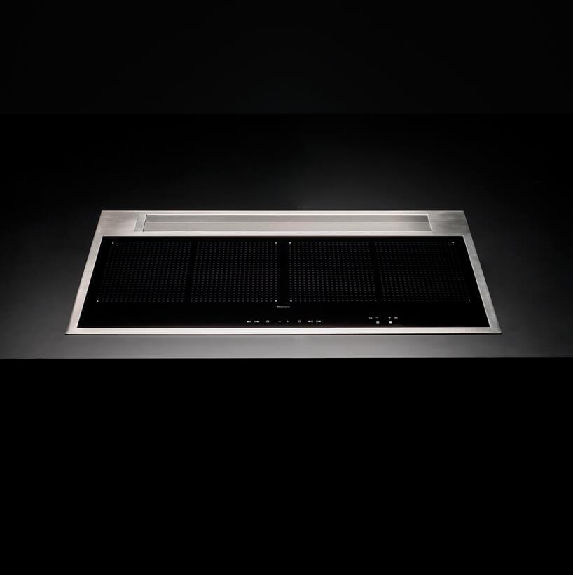 czarna zmetalową ramką płyta indukcyjna ze zintegrowanym okapem podczas gotowania wczarnym blacie