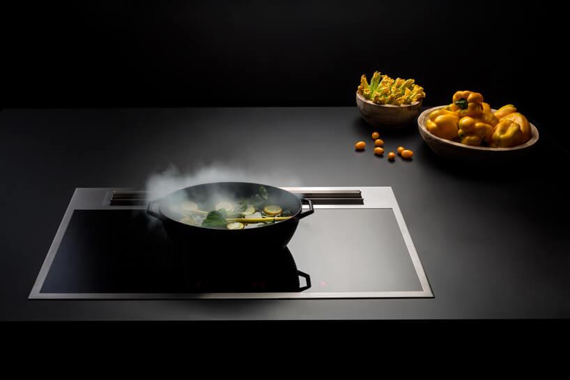 czarna zmetalową ramką płyta indukcyjna ze zintegrowanym okapem podczas gotowania podczas gotowania żółtych warzyw