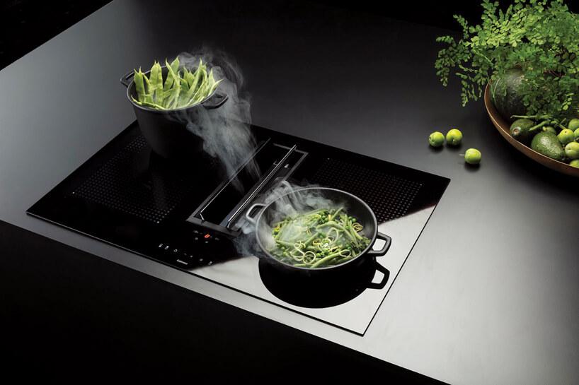 czarna płyta indukcyjna ze zintegrowanym okapem podczas gotowania zielonych warzyw wdwóch garnkach