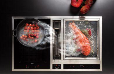 czarna ze srebrną ramką płyta indukcyjna ze zintegrowanym okapem podczas gotowania czerwonej ryby i pomidorów