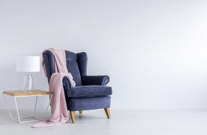 fioletowy fotel obok stolika na tle jasnej ściany