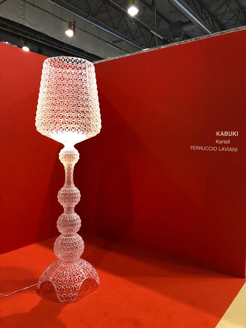 wysoka lampa wykonana zmałych koralików na tle czerwieni