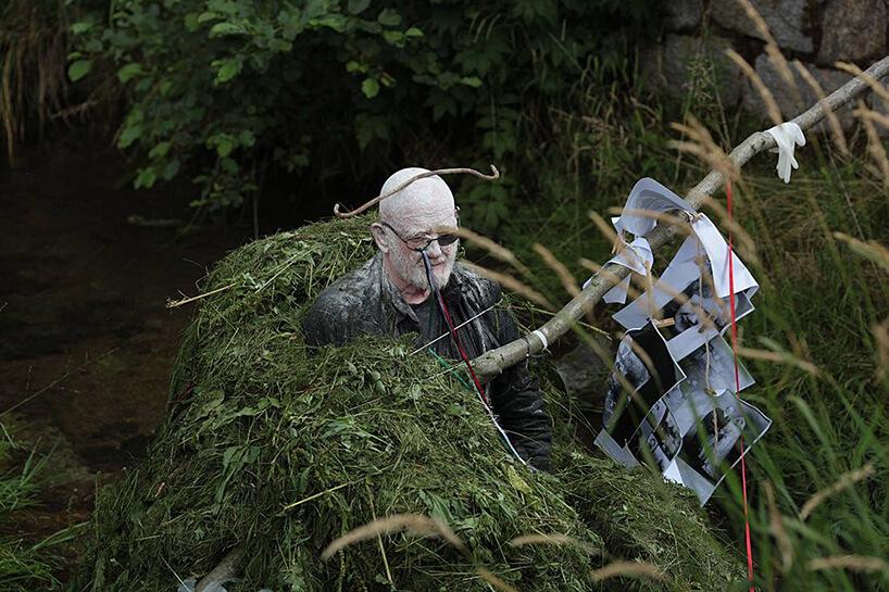 artysta przysypany ściętą trawą