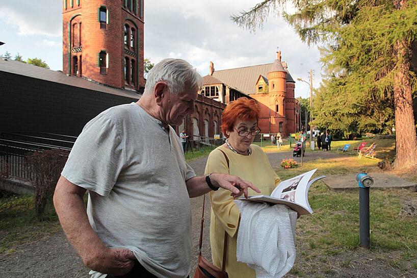 widzowie przeglądający broszurę