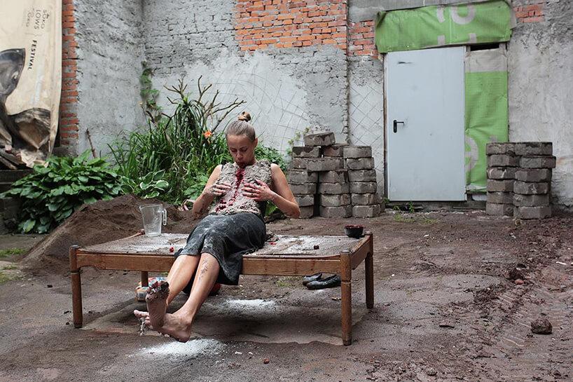 performance artysty siedzącego na ławie