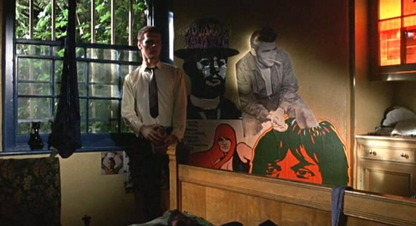 mężczyzna stojący woknie pokoju zdużymi plakatami