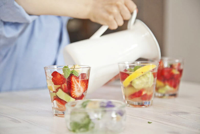 szklanki pełne owoców zalewane wodą zdzbanka