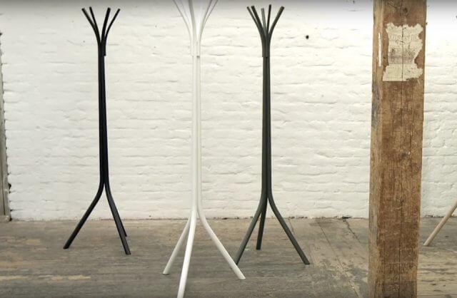 biały i dwa czarne wieszaki przy ścianie z licówki