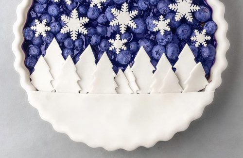 ciasto z jagodami w lukrowej formie i zdobieniami w lukrowe płatki śniegu i choinki