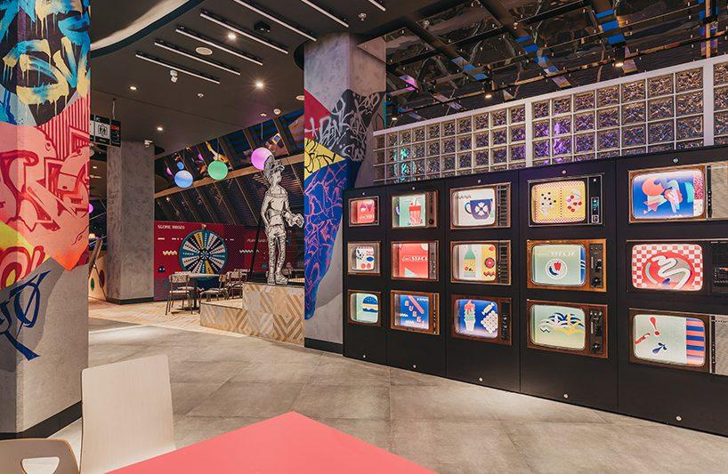 Foodstacja wPasażu Grunwaldzkim widok na kolorowe telewizory na ścianie