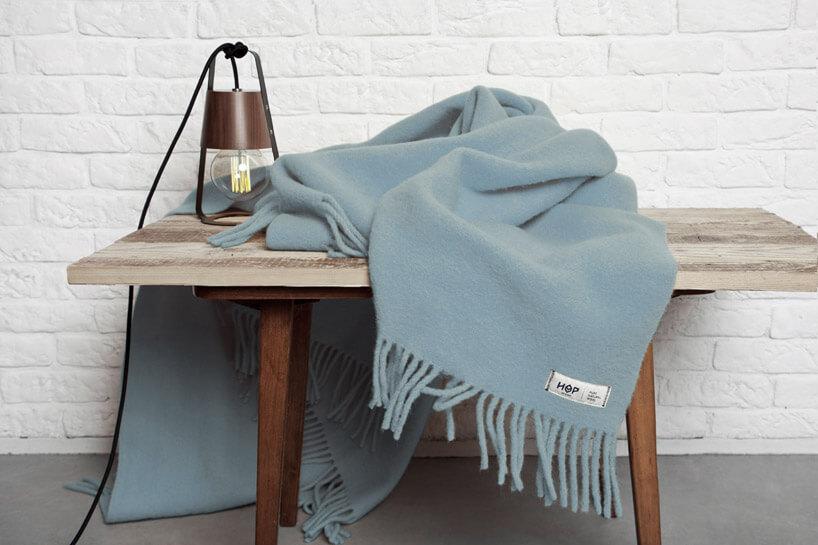 niebieski koc leżący na drewnianym stole zlampą